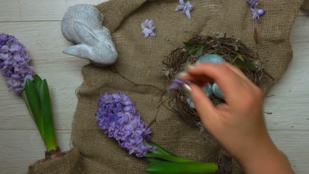 Rukou zdobí stůl s velikonoční hnízdo s barevnými vejci a květiny
