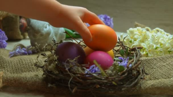 Childs hand lays colored egg in in the Easter nest
