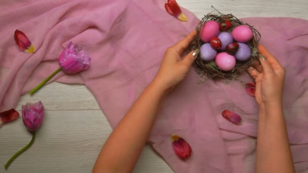 Hands put on the table an Easter nest with colored eggs and a tray with tea