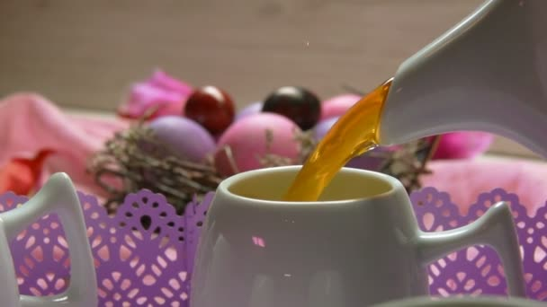 a tea poured in the cup on the background of colored pink Easter egg lies