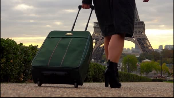 a tourist woman with a suitcase is walking to the Eiffel Tower