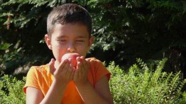 Boy smells the aroma of peach