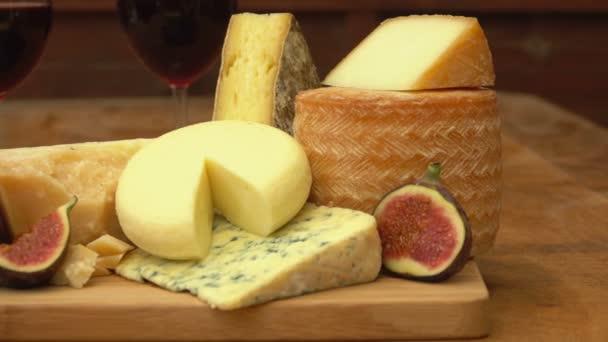 Kousky sýrů, vín a fíky na dřevěný stůl