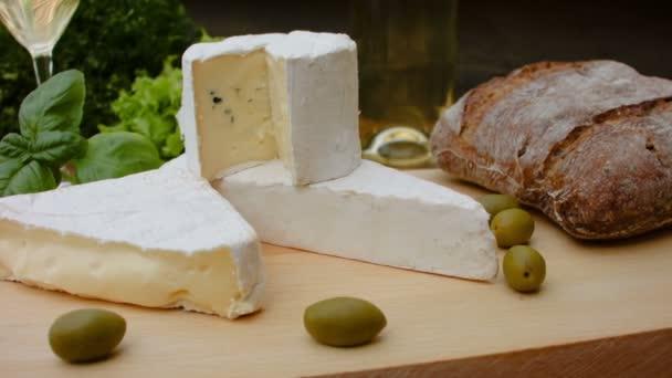 French brie cheese with bread, olives, basil and parsley