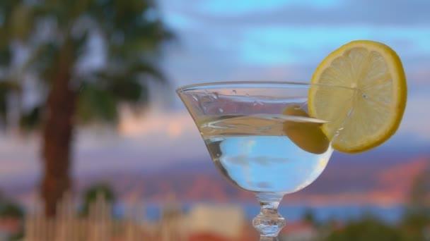 Olive esik egy pohár martini és citrommal