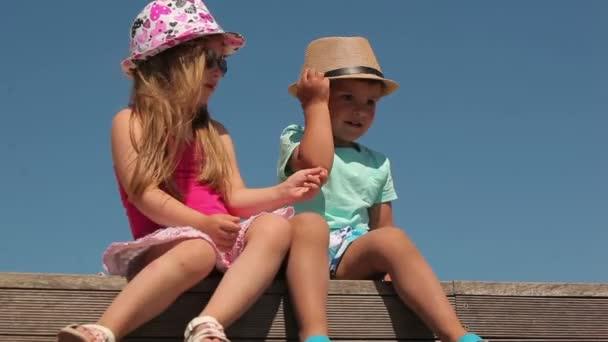 Malý chlapec a dívka sedí na lavičce