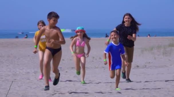 Pět šťastných dětí v čistých šatech utíká z moře