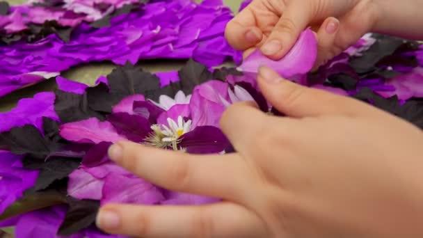 Florist makes composition of purple flower petals