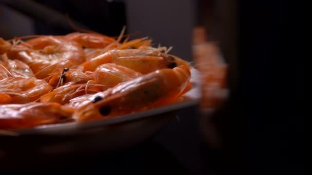 Krevety padají na talíř na černém pozadí