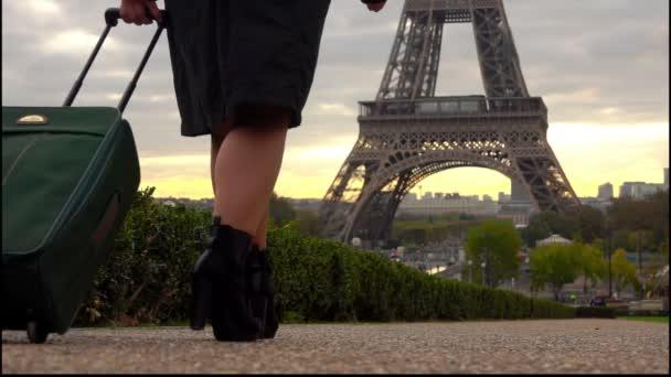 Businesswoman is walking towards Eiffel Tower