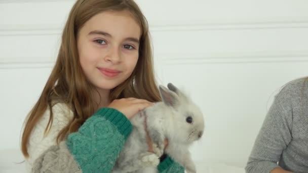 schönes Mädchen streichelt ein süßes kleines Kaninchen