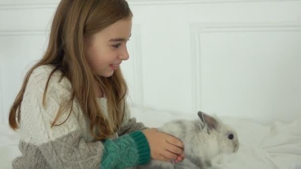 schönes Mädchen umarmt ein graues, flauschiges Kaninchen