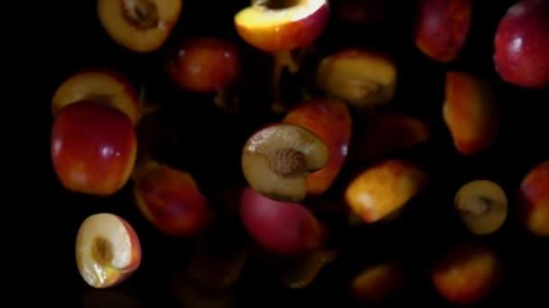 Félig őszibarack ugrál a fröccsenő gyümölcslé a fekete háttér