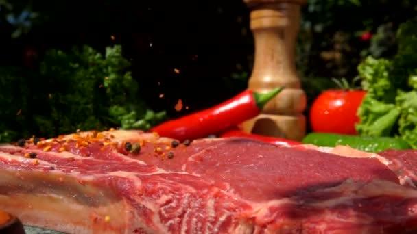 Gemischter Pfeffer und Gewürze fallen auf das rohe Fleischsteak