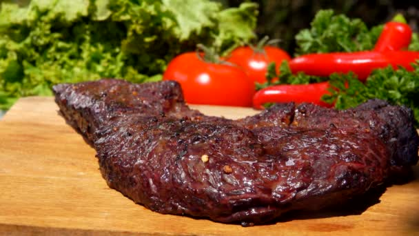 Lahodně připravené maso steak na desce na pozadí zeleniny