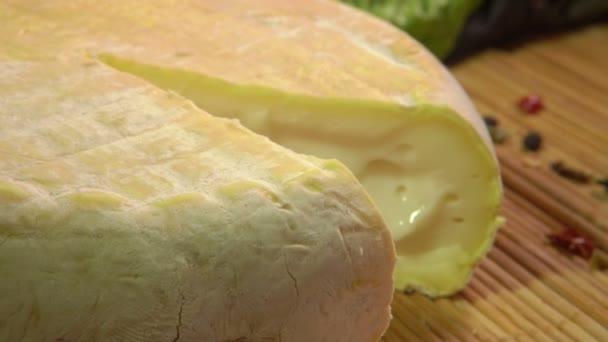 Detailní záběr francouzského měkkého krémového sýra na dřevěné desce