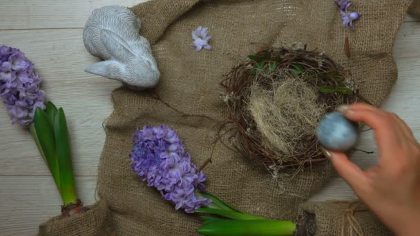 Hibiscus tea-dyed Easter egg placed in the nest on the background of flowers