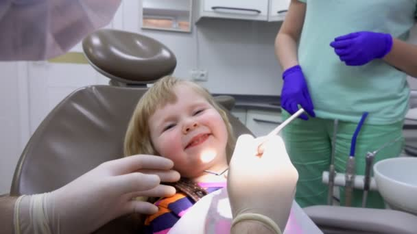 Dentist examines teeth of a little girl with a small mirror