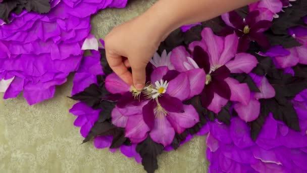 Florist makes a composition of purple flower petals