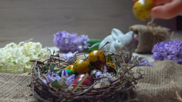 Childss hand puts a small colored Easter egg into the nest