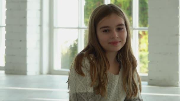 Gyönyörű hosszú hajú lány mosolyog és ül egy fehér napfényes csarnokban