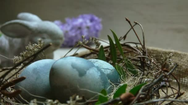 Close up of Hibiscus-dyed Easter egg in the nest on the background of flowers