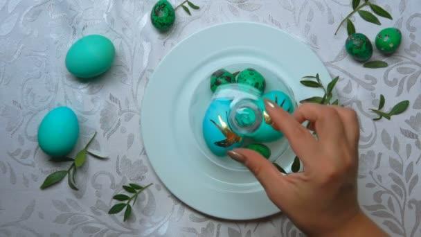Ruce sundají skleněnou kupoli z bílého talíře se zelenobarevnými velikonočními vejci