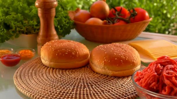 Cesam Bun padá na stůl. Složky pro přípravu hamburgerů