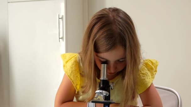 Cute girl is looking look through the microscope and to the camera