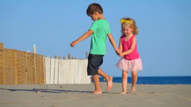 Malý chlapec a dívka v růžové sukni hrají a chodí po pláži