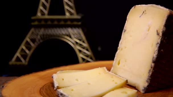 Vidlička vezme kus francouzského sýra z dřevěné desky