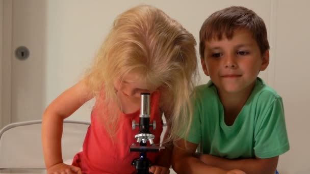Boy is looking to the camera while a cute girl is looking through a microscope