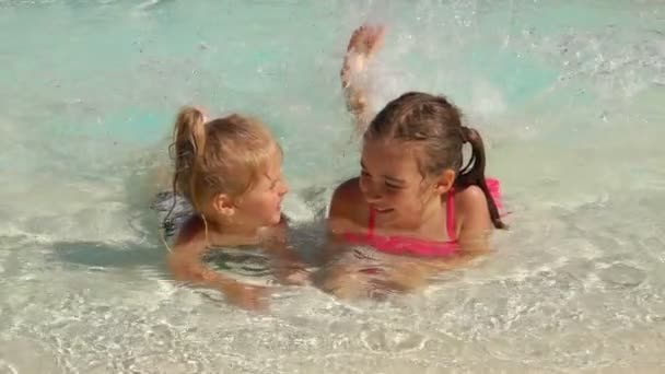 Two sibling girls lay on stomach and splash water in the pool with their legs