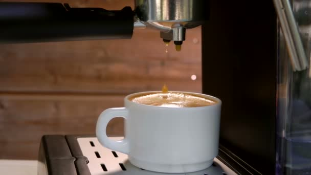 Last drops of coffee are falling into cup with espresso from the coffee machine