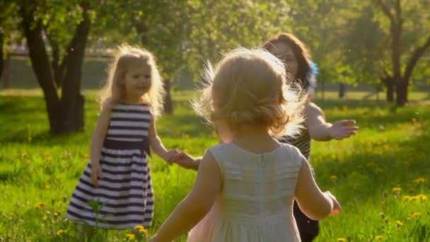Mother is playing with two little girls on the lawn in the sunlit apple garden