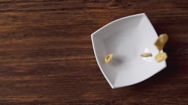 Kukuřičné vločky padající v bílé míse s copyspace vlevo na dřevěný stůl
