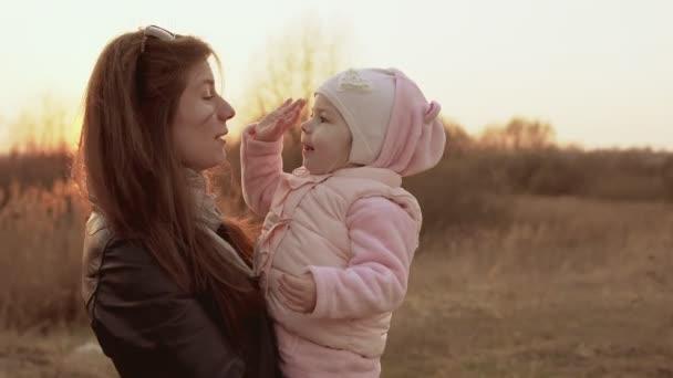 Máma hraje s dcerou a baví proti západu slunce na obloze