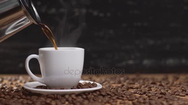 Nalil kávu v bílých pohár obklopený kávová zrna na tmavém pozadí. 4k