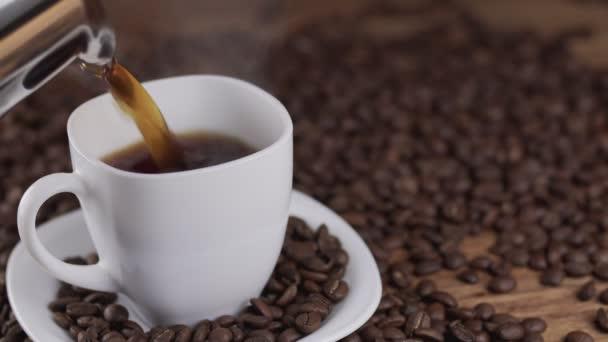 Nalil kávu z kávovaru bílých pohár obklopený kávová zrna v rozlišení 4k Uhd