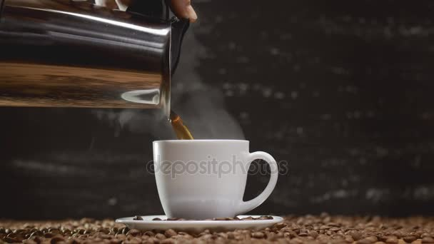 Pouring coffee from coffee pot in white cup surrounded by coffee beans in 4k UHD
