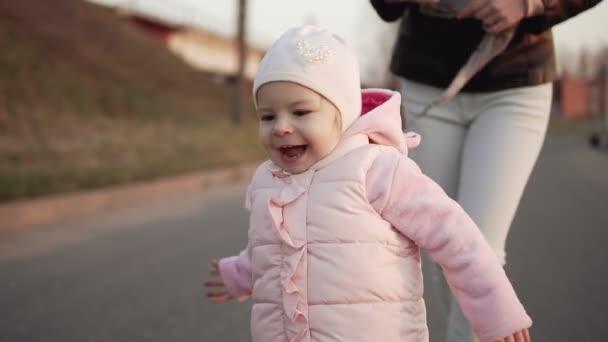 Dítě je běh pryč od matky venku. Žena dítě baví při západu slunce
