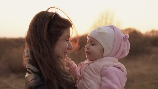 Mom plays with daughter and having fun against of sunset sky. Slow motion shot