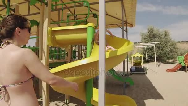 Mother and little daughter have fun at playground at sea beach in sunny day