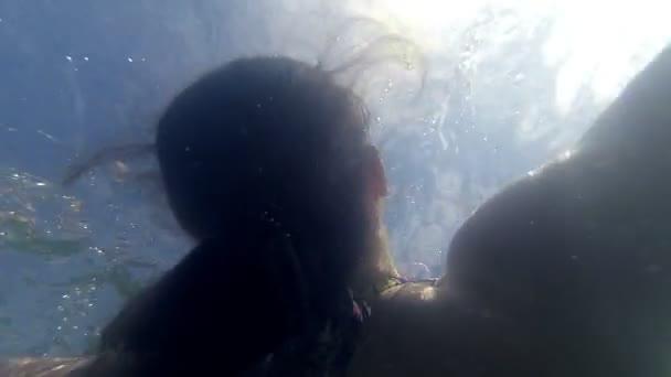 Mladá šťastná žena uvolňující na nafukovací matraci v moři