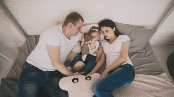 Fiatal családi szórakozást fedett. Járműcsalád-koncepció. Boldog családi élvezi az ágyon