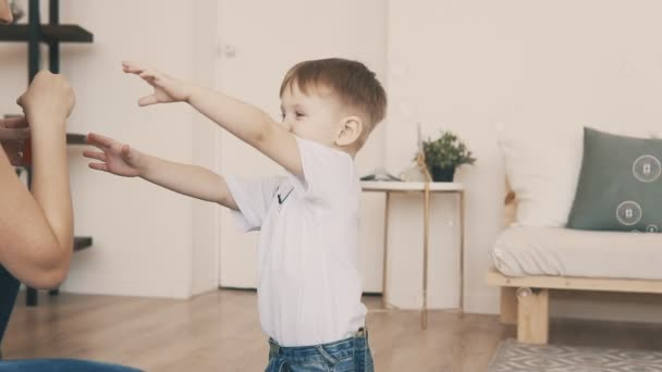 Little son in jeans and white t-shirt has fun with bubbles with young mother