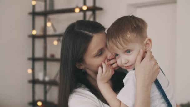 Malého syna v náručí matky doma. Usmívající se matka s dítětem