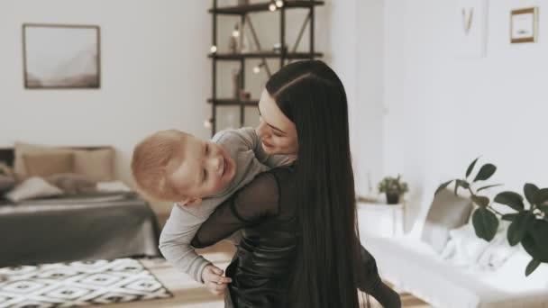 Malou dceru v náručí matky doma. Usmívající se matka s dítětem