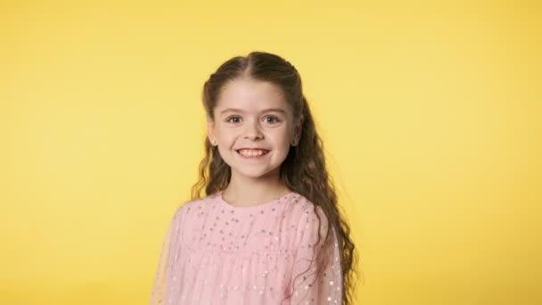 Boldog kislány mosolyog a kamerába. Portré gyönyörű kislány rózsaszín ruhában sárga háttér. Közepes felvétel lassított felvételben. 4k, Uhd 60 Fps