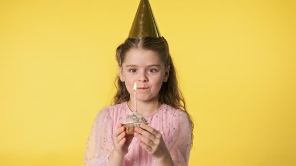 Šťastná krásná dívka v růžových šatech hraje s narozeninovým dortíkem a směje se. Holčička v čepici na večírku sfoukla svíčku na žlutém pozadí. Narozeninový koncept. Střední záběr v 4k Uhd